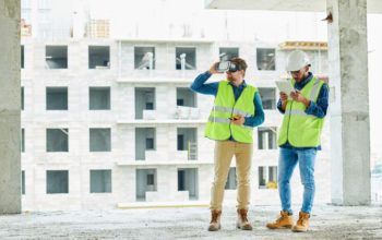 Construction workers survey the incomplete floor of a multiple story building